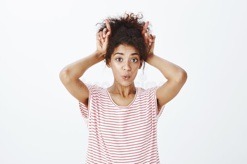 Portret składa wargi i trzyma palce wskazujących zasięrzutni śliczna czuła ciemnoskóra dziewczyna w modnej pasiastej koszulce, fotografia stock