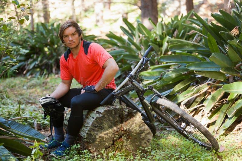 Portret skołowany męski halny rowerzysta relaksuje na drzewnym bagażniku w lesie zdjęcia stock