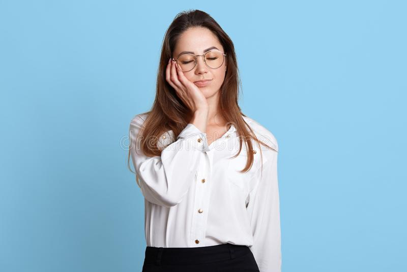 Portret skołowany sypialny bizneswoman trzyma jej głowę z zamkniętymi oczami na prawej ręce Atrakcyjna młoda kobieta cieszy się k zdjęcie stock