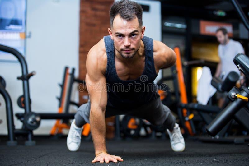 Portret skoncentrowany młody sportowiec wykonujący ćwiczenia na desce zdjęcia stock
