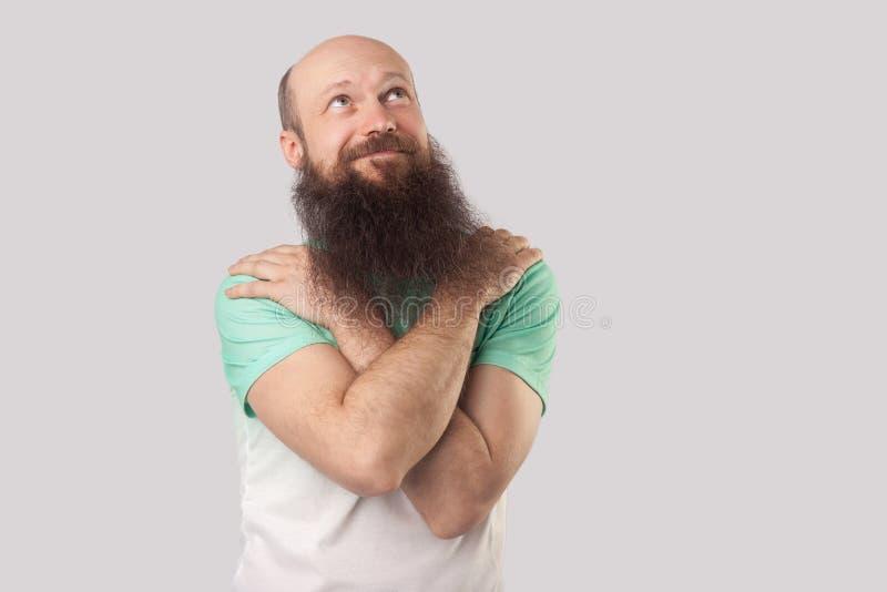Portret smiley, marzycielski w średnim wieku łysy mężczyzna z długą brodą w zielonej koszulki pozycji, przytulenie himself, patrz zdjęcie stock