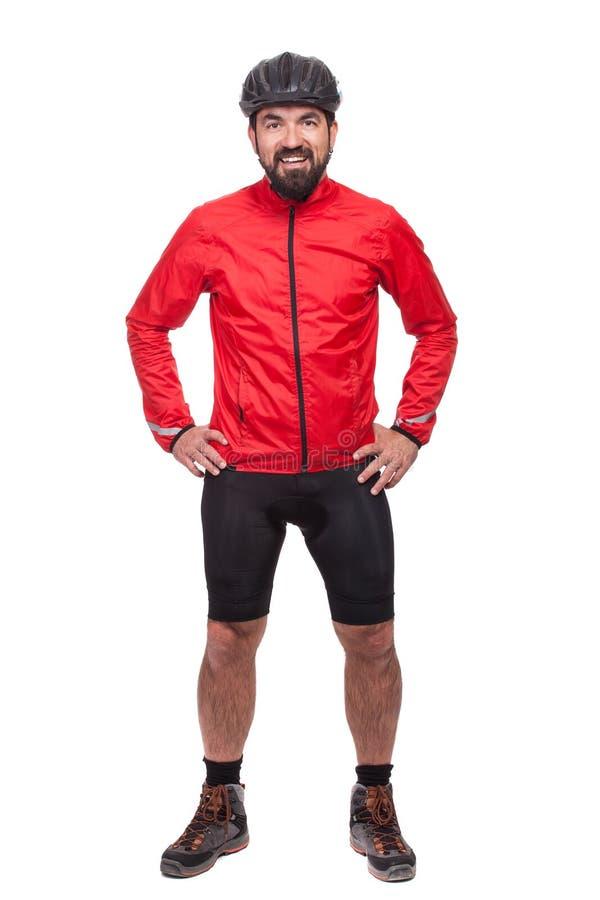 Portret smilling bicyclist z hełmem i czerwieni kurtką, odizolowywający na bielu zdjęcie royalty free