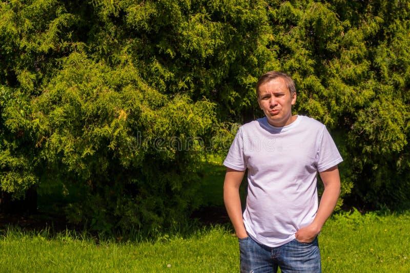 Portret smutny m??czyzna w bia?y koszulki sta? outside w parku zdjęcie stock