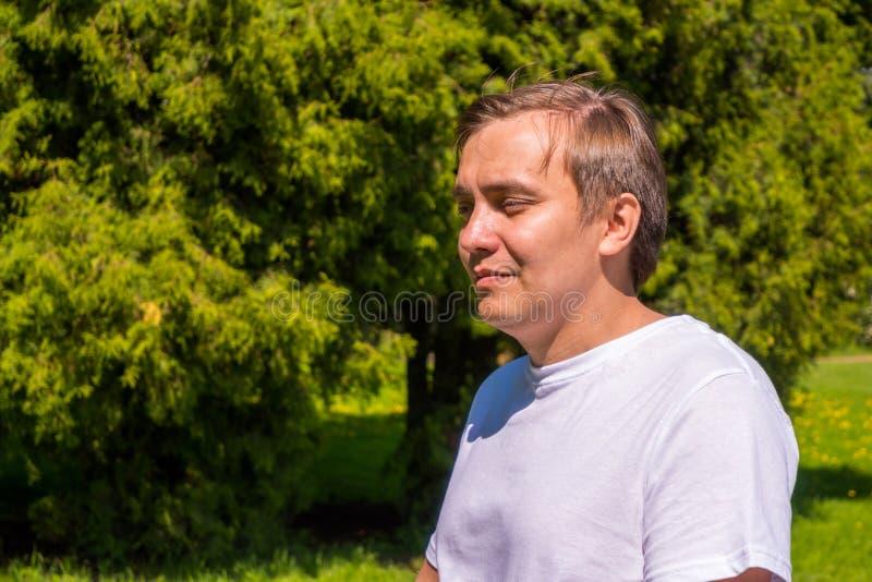 Portret smutny m??czyzna w bia?y koszulki sta? outside w parku fotografia royalty free