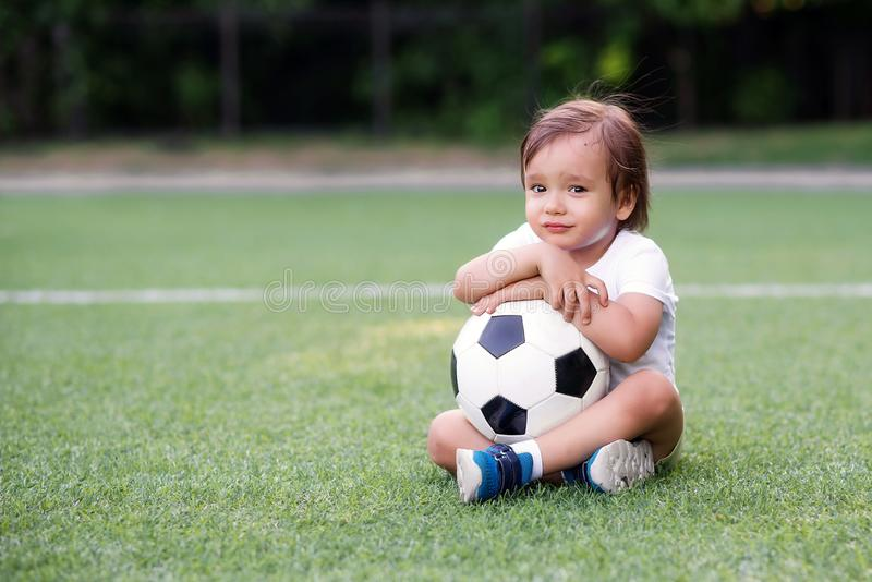 Portret smutny nieszczęśliwy chłopiec obsiadanie na boisku piłkarskim i mieniu z oba ręki lub obejmowanie piłki nożnej piłka Maj  zdjęcia royalty free