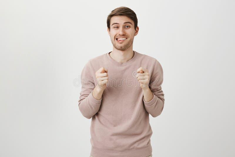 Portret speelse aantrekkelijke kerel die fig. met beide handen tonen terwijl uit het plakken van tong en het glimlachen met tevre stock fotografie