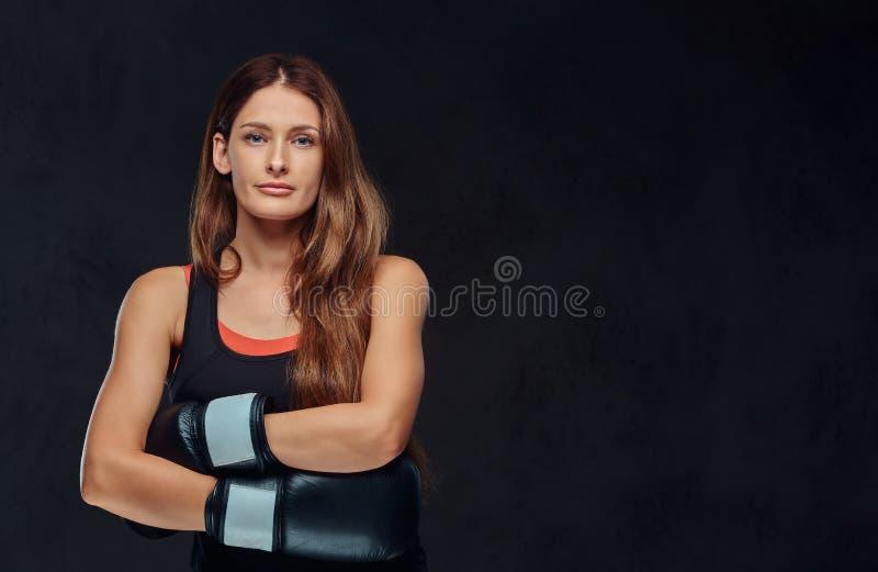 Portret sportive kobieta jest ubranym bokserskie rękawiczki pozuje z krzyżować rękami w studiu ubierał w sportswear odosobniony obraz stock