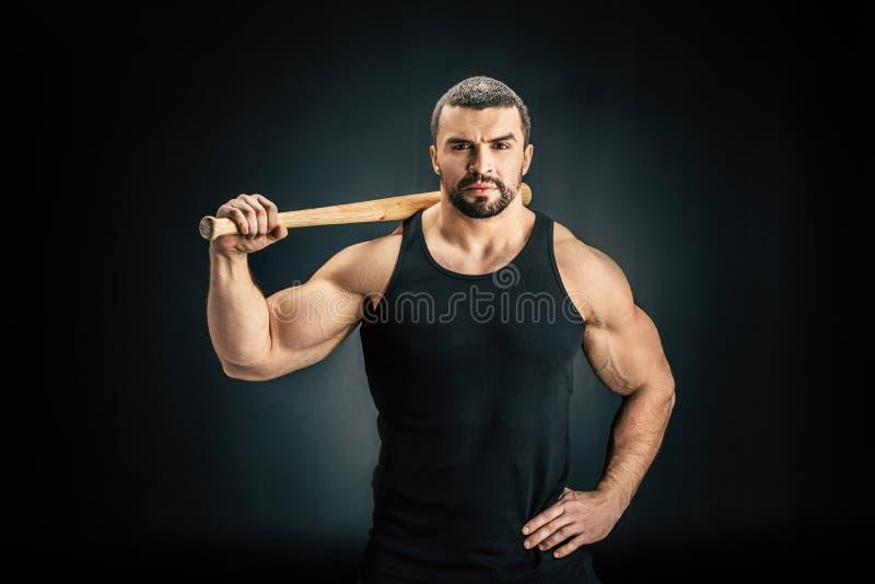 portret sportive mężczyzna stać akimbo z kijem bejsbolowym na ramieniu zdjęcie royalty free