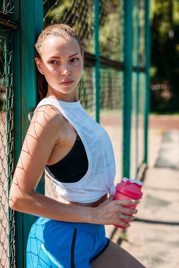 Portret sporty młoda seksowna kobieta z butelką chłodno woda na lato sportów polu zdjęcia royalty free