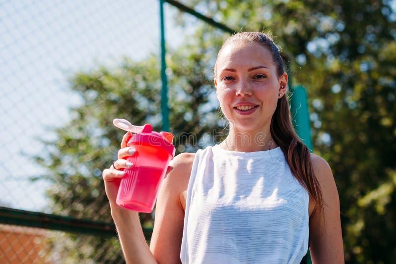 Portret sporty młoda seksowna kobieta z butelką chłodno woda na lato sportów polu zdjęcie royalty free