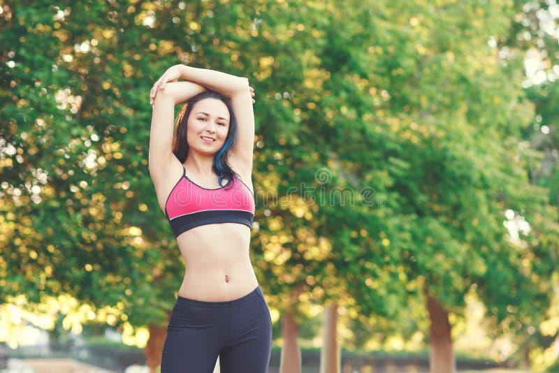 Portret sprawności fizycznej schudnięcia młoda dziewczyna po Jogging w plenerowym parku na jaskrawym słonecznym dniu Pojęcie akty zdjęcie stock