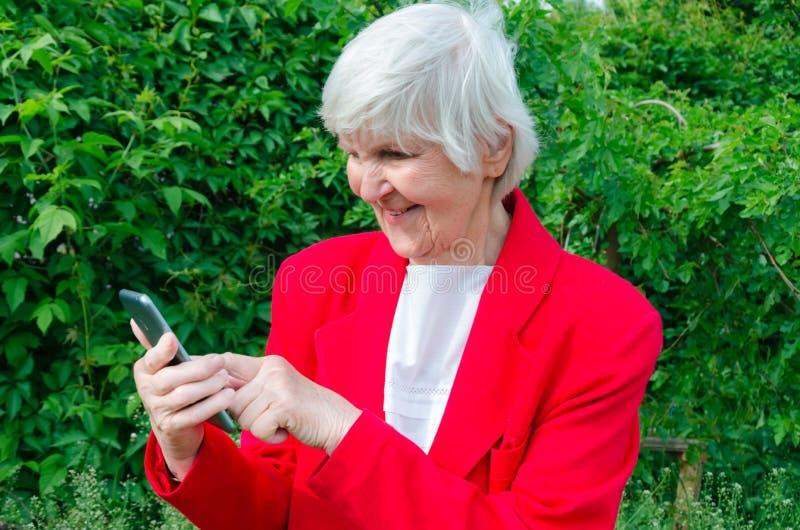 Portret stara dama, babcia robi selfie outdoors przy słońce dniem nowożytny babcia palca dotyk ekran sensorowy jej telefon zdjęcia stock
