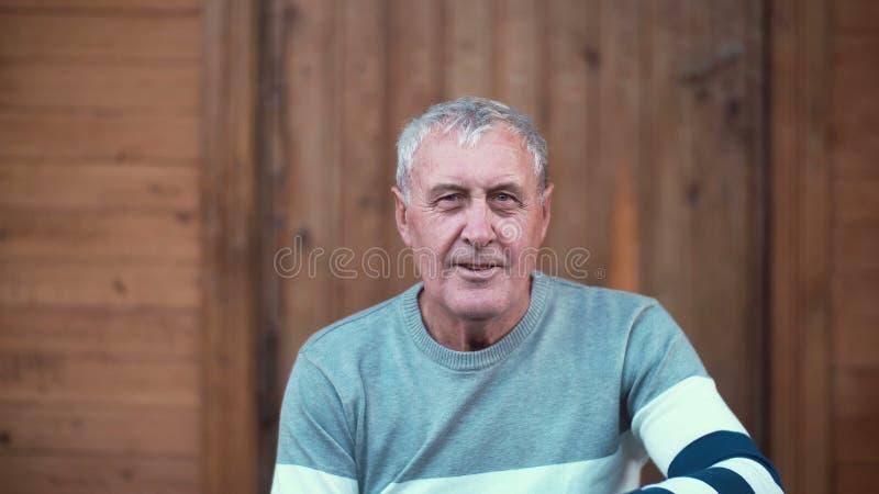 Portret starego człowieka obsiadanie na ganeczku dom Emeryt patrzeje kamera, ono uśmiecha się i dymić, 4K obraz royalty free