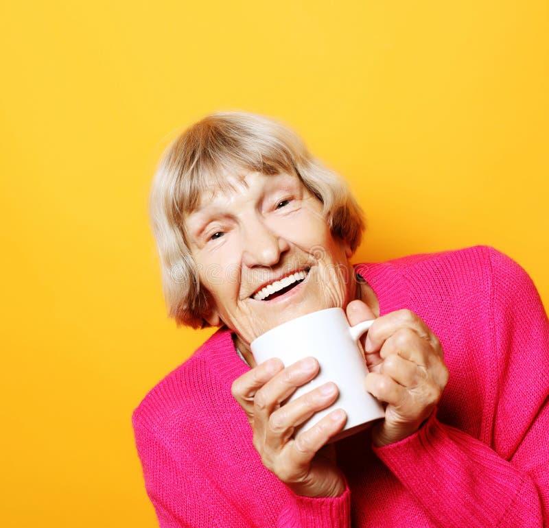 Portret starej podekscytowanej kobiety uÅ›miechajÄ…cej siÄ™ Å›miesznie, trzymajÄ…cej filiżankÄ™ kawy, herbaty, napoju na żółty zdjęcie royalty free
