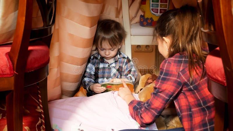 Portret starej siostry czytelnicza książka z berbecia bratem w namiocie przy sypialnią zdjęcia stock