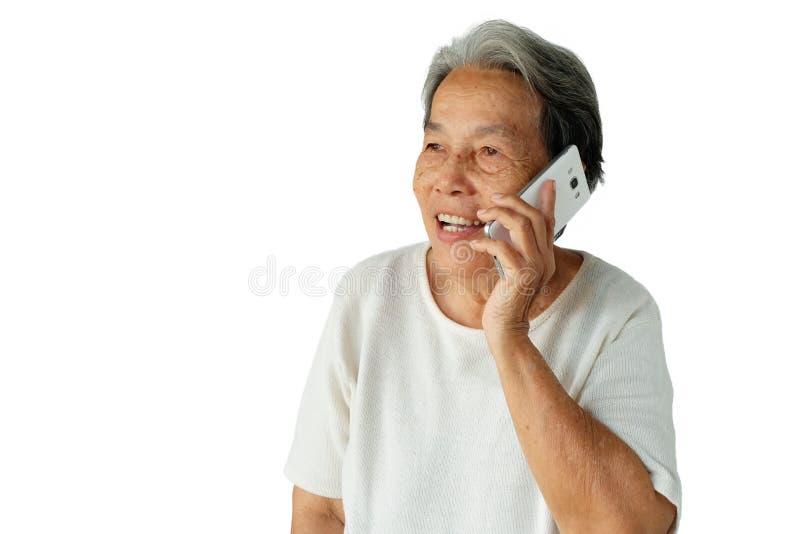 Portret starsza azjatykcia kobieta używa telefon komórkowego z uśmiechem odizolowywającym na białym tle zdjęcie royalty free