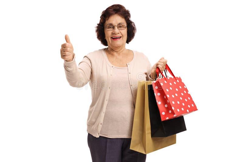 Portret starsza dama z torbami na zakupy daje kciukowi w górę zdjęcie royalty free