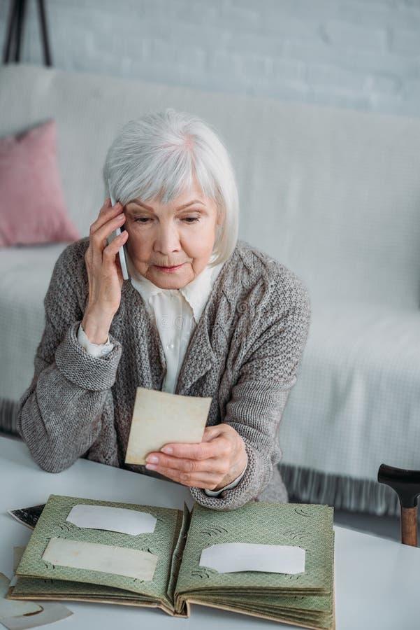 portret starsza kobieta opowiada na smartphone z fotografią w ręce fotografia stock