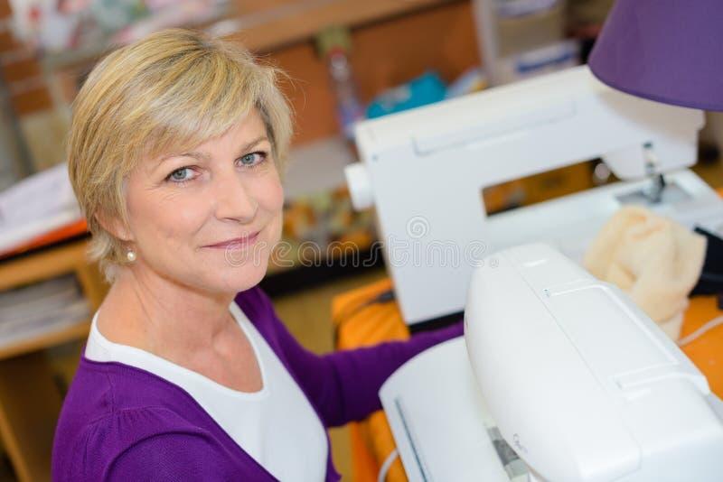 Portret starsza kobieta używa szwalną maszynę obraz royalty free