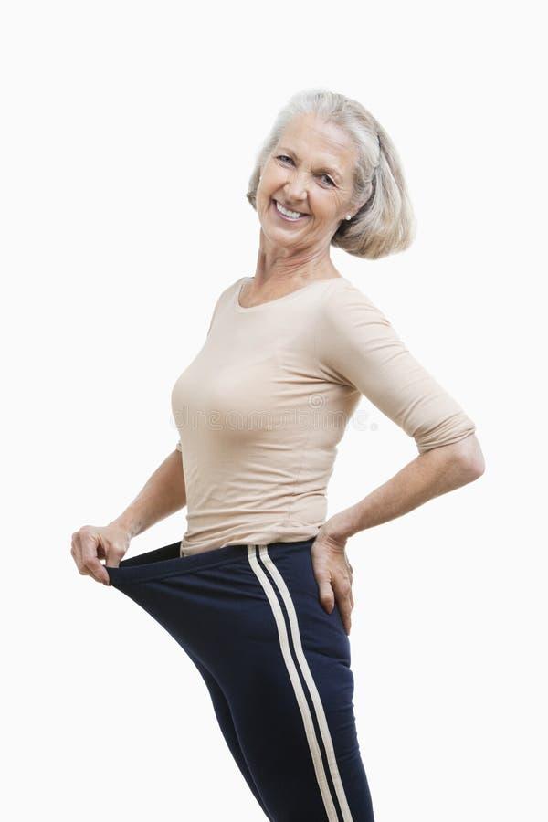 Portret starsza kobieta w dużych rozmiarów spodniach przeciw białemu tłu fotografia stock
