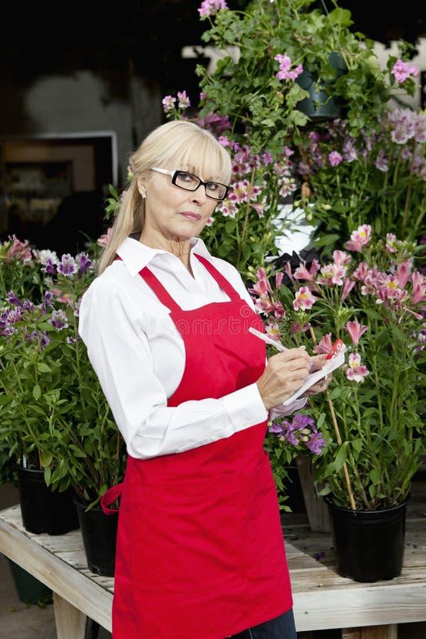 Portret starsza kwiaciarnia robi notatkom w ogrodowym centrum zdjęcia stock