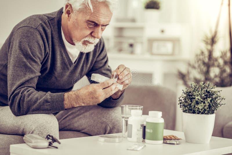 Portret starsze chore mężczyzny mienia pigułki boksuje w rękach obraz stock