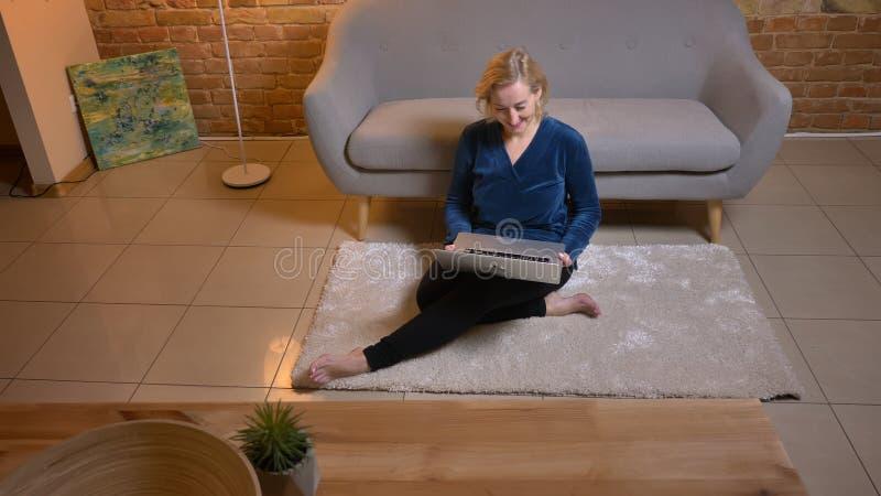Portret starszy caucasian damy obsiadanie na podłodze i dopatrywanie w laptop szczęśliwie w wygodnej domowej atmosferze zdjęcie stock
