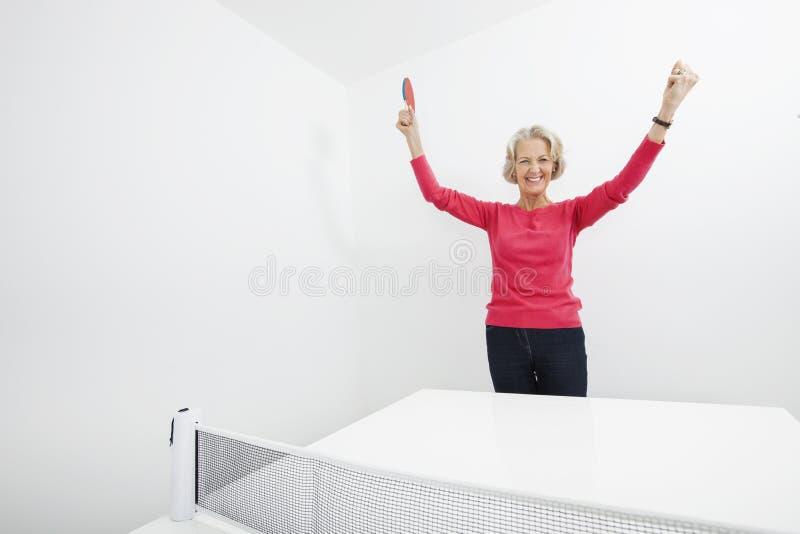 Portret starszy kobieta stołu gracz w tenisa z rękami podnosił odświętności zwycięstwo zdjęcie royalty free