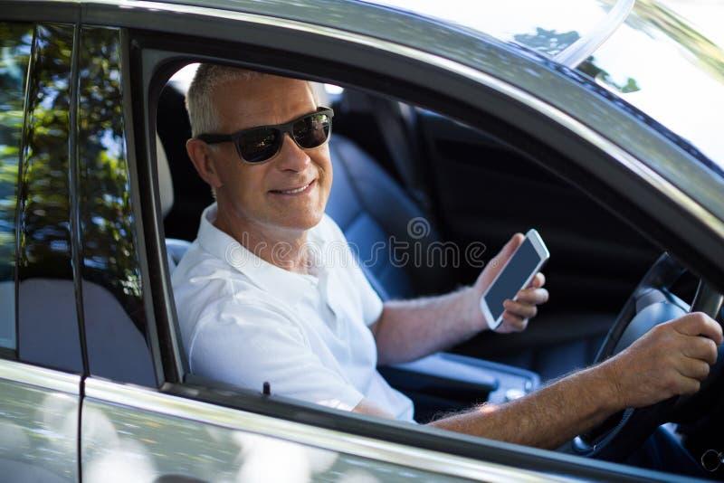Portret starszy mężczyzna używa telefon komórkowego w samochodzie zdjęcie royalty free