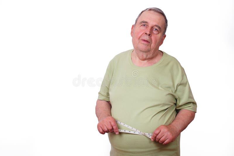 Portret starszy starszy z nadwagą mężczyzna z pomiarową taśmą ar obrazy stock