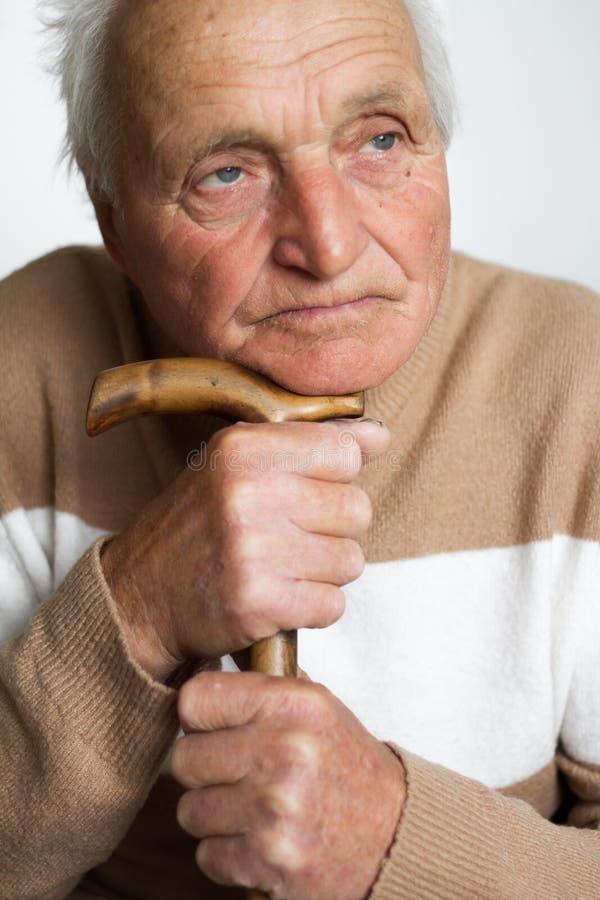 Portret stary smutny mężczyzna który stawia jego głowę na rękojeści drewniana trzcina obrazy royalty free