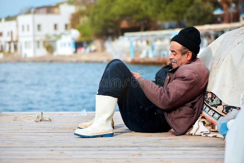 Portret stary Turecki rybaka obsiadanie na doku na zima dniu w Bodrum, Gumusluk, Mugla, Turcja zdjęcia stock