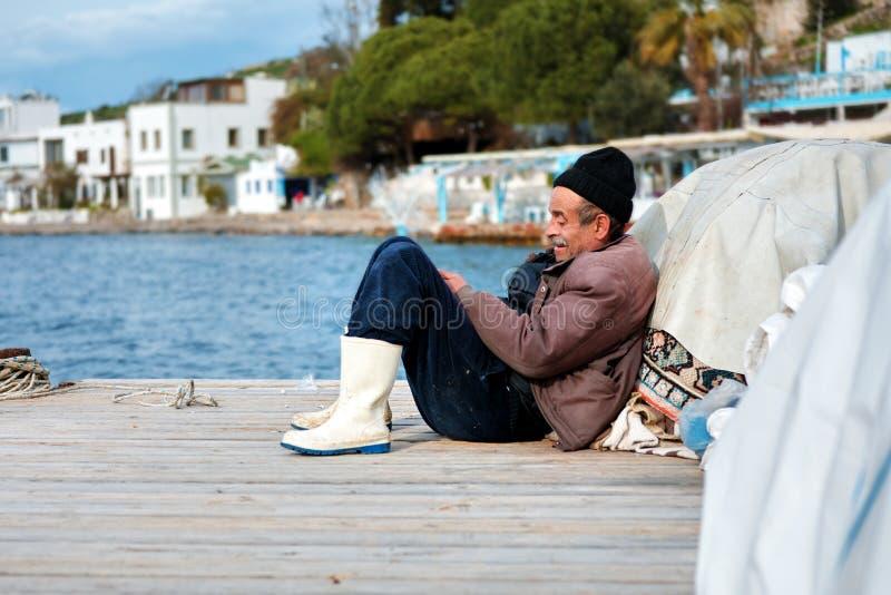Portret stary Turecki rybaka obsiadanie na doku na zima dniu w Bodrum, Turcja obrazy royalty free