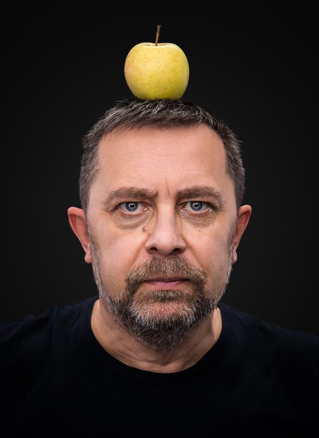 Mężczyzna z zielonym jabłkiem na jego głowie zdjęcie royalty free