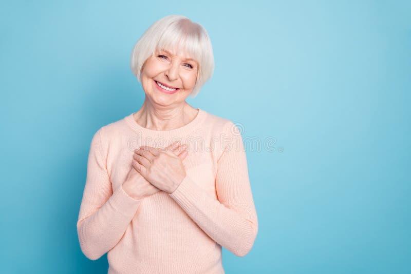 Portret stawia jej palmy na klatce piersiowej ono uśmiecha się pozytywna kobieta będący ubranym pastelowego pulower odizolowywają zdjęcia stock