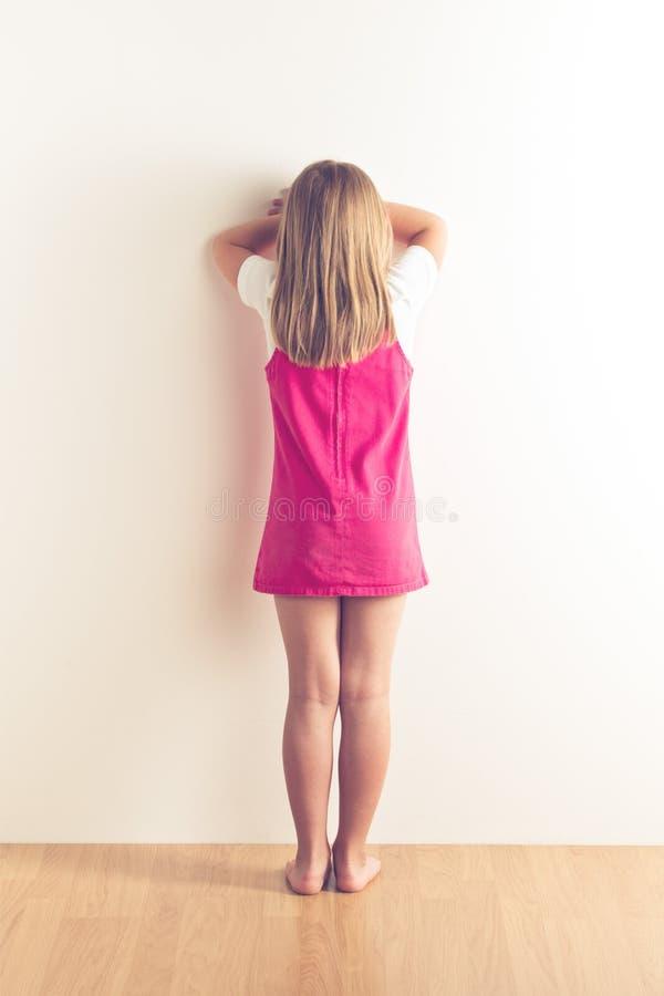 Portret stoi blisko ściany smutna mała dziewczynka zdjęcia royalty free
