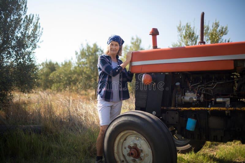 Portret stoi blisko ciągnika w oliwki gospodarstwie rolnym ufna kobieta zdjęcie royalty free