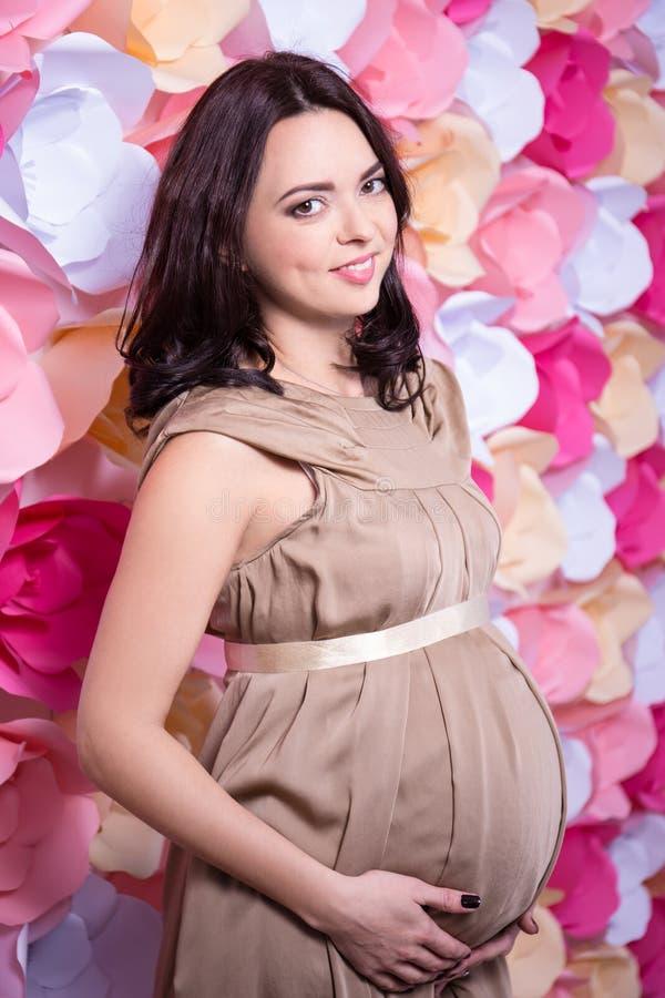 Portret stoi nad kolorowym kwiatem uśmiechnięty kobieta w ciąży fotografia royalty free