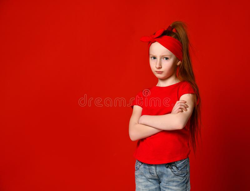 Portret stoi z fałdowymi rękami i patrzeje kamerę śliczny dziewczyny spęczenie w czerwonej kamizelce, fotografia royalty free