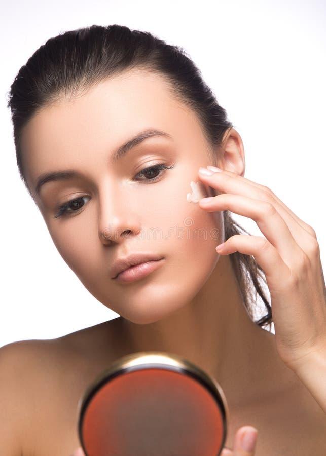 Portret stosuje moisturizer śmietankę na jej ładnej twarzy młoda kobieta - biały tło Moda i piękno zdjęcie royalty free