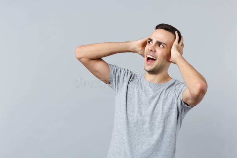 Portret straszący krzyczący młody człowiek patrzeje na boku w przypadkowych ubraniach, stawia ręki na głowie odizolowywającej na  zdjęcia royalty free