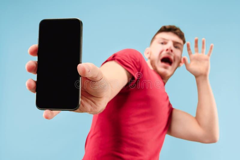 Portret straszący mężczyzna z telefonem na błękicie zdjęcia royalty free