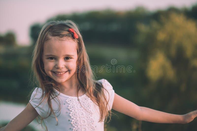 Portret strzelał śliczna mała dziewczynka ono uśmiecha się w łące obrazy royalty free