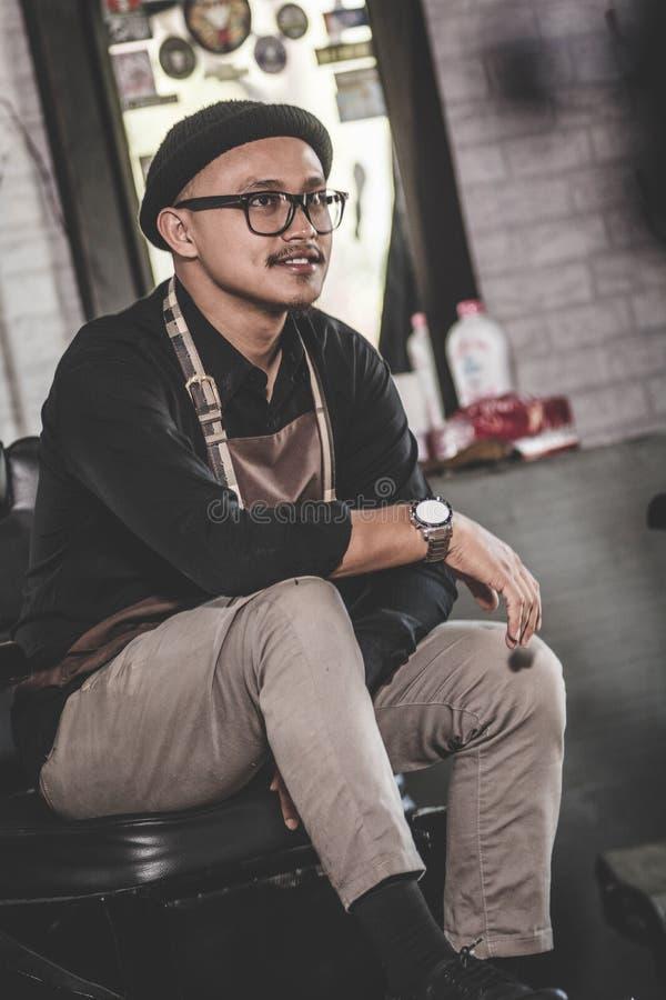 Portret stylisty fryzjera męskiego obsiadanie przy zakładu fryzjerskiego krzesłem fotografia stock