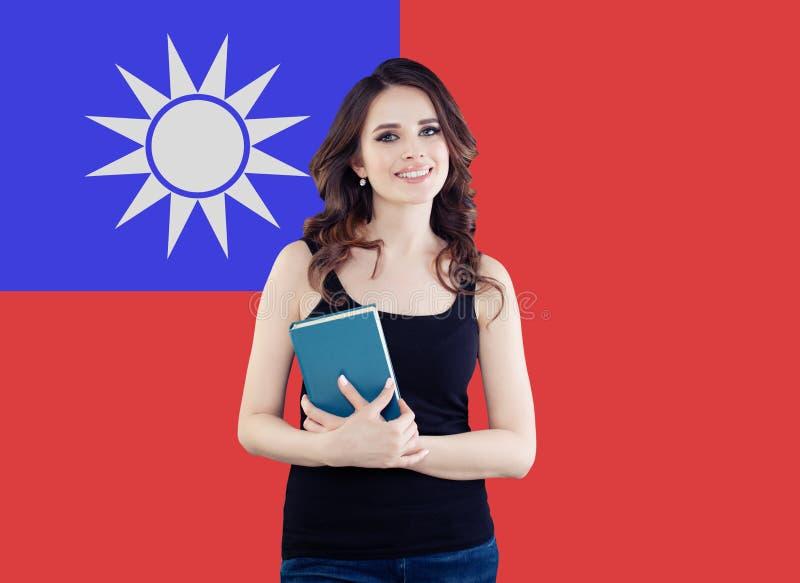 Portret szczęśliwa ładna dziewczyna przeciw Tajwańskiemu chorągwianemu tłu Młoda kobieta uczy się chińskiego języka i podróżuje w obraz stock