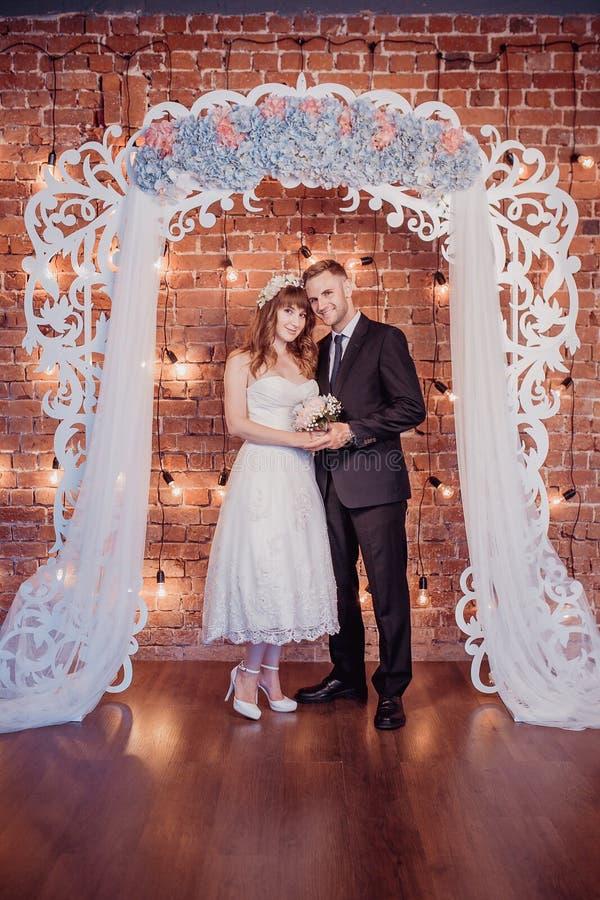 Portret szczęśliwy młody państwo młodzi w klasycznym wnętrzu blisko ślubnego łuku z kwiatami Dzień ślubu, miłość temat najpierw obraz royalty free
