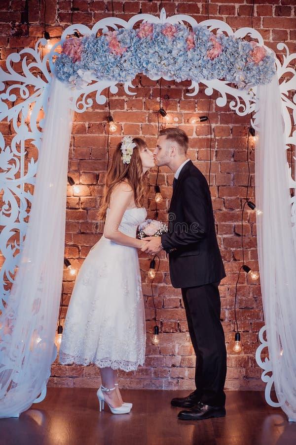 Portret szczęśliwy młody państwo młodzi w klasycznym wnętrzu blisko ślubnego łuku z kwiatami Dzień ślubu, miłość temat najpierw zdjęcia royalty free