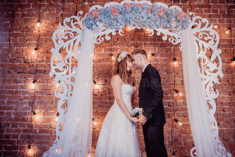 Portret szczęśliwy młody państwo młodzi w klasycznym wnętrzu blisko ślubnego łuku z kwiatami Dzień ślubu, miłość temat najpierw obrazy stock