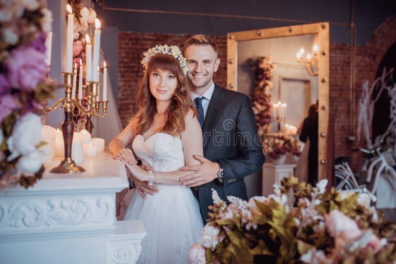 Portret szczęśliwy młody państwo młodzi w klasycznym wnętrzu blisko graby z kwiatami Dzień ślubu, miłość temat dzień pierwszy fotografia stock