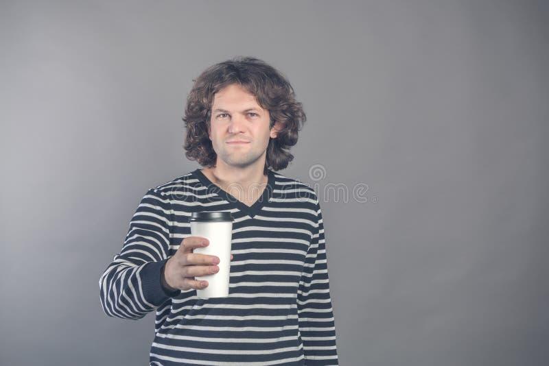 Portret szczęśliwy przystojny ciemny z włosami kędzierzawy mężczyzna w pasiastym pulowerze z papierową filiżanką odizolowywającą  obraz stock